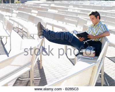 Male student on bench reading - Stock Photo