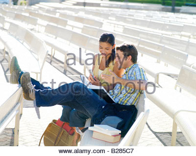 Couple on bench outdoors, woman with mobile phone, smiling - Stock Photo