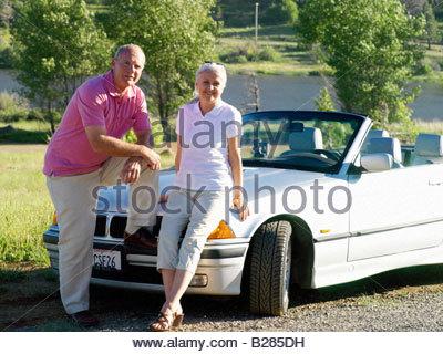 Couple on bonnet of convertible car, portrait - Stock Photo