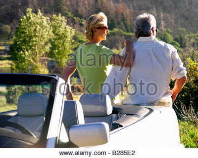 Couple by car looking at scenery, rear view - Stock Photo