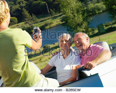 Woman taking photograph of senior couple by river - Stock Photo