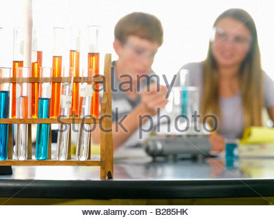 Students (12-14) with chemistry experiment, focus on beakers - Stock Photo