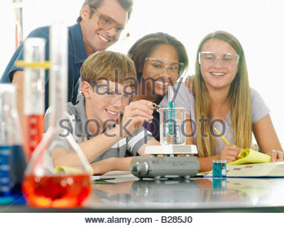 School students (12-14) and teacher with experiment in science class - Stock Photo