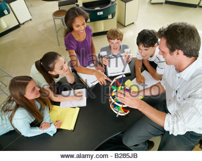 School teacher showing students (12-14) model in classroom, elevated view - Stock Photo