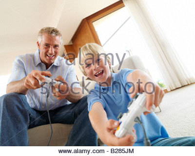 Father and son (8-10) playing video game, portrait, low angle view - Stock Photo