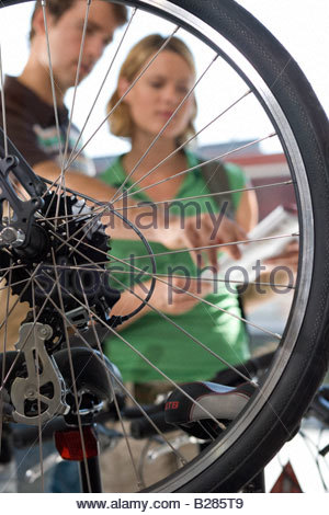 Man and woman in bicycle shop, view through wheel - Stock Photo