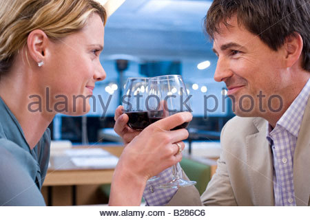 Couple proposing toast with wine glasses in restaurant, close-up - Stock Photo
