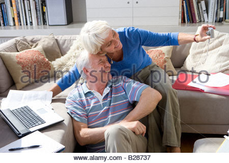 Senior couple taking photograph of themselves, smiling - Stock Photo