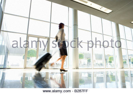 Businesswoman with luggage, low angle view (blurred motion) - Stock Photo
