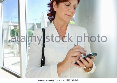 Businesswoman with electronic organiser, close-up - Stock Photo