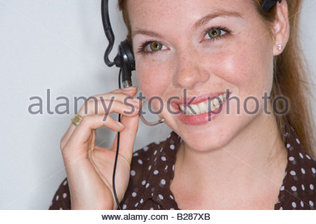 Woman with headset, smiling - Stock Photo