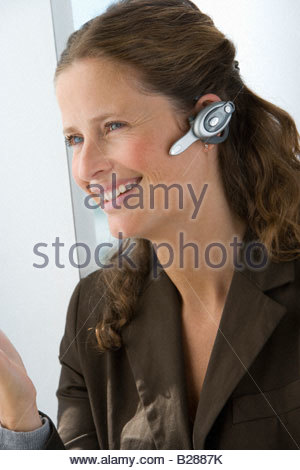 Businesswoman with hands-free cell phone headset - Stock Photo