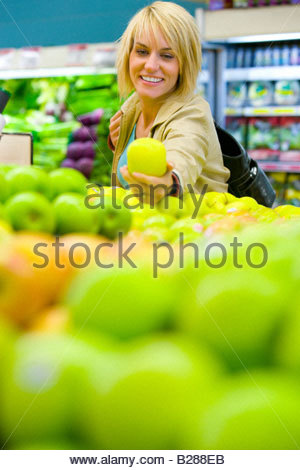 Woman choosing apples in grocery store - Stock Photo