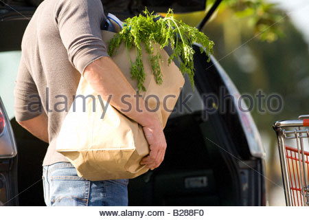 Man loading groceries into rear of car - Stock Photo