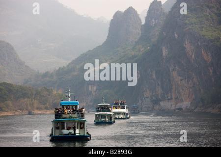 Tourist boats travel along Li River between Guilin and Yangshuo China - Stock Photo