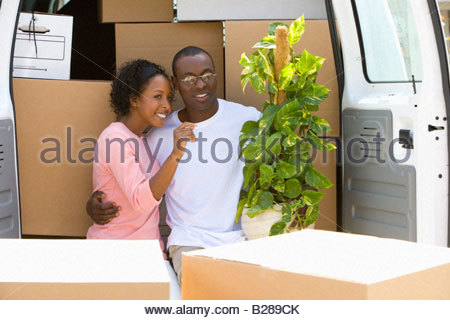 Couple unloading boxes from van - Stock Photo