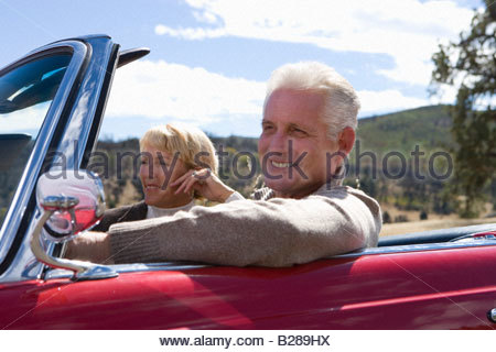 Couple on road trip in convertible - Stock Photo