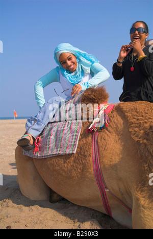 Young Omani woman taking a camel ride at Al Sawadi Beach Resort - Stock Photo
