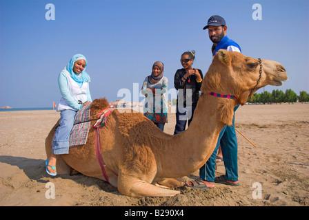 Young Omani woman gets onto a sitting camel held by Omani man on Al Sawadi beach - Stock Photo