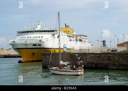 The Cote D albatre ferry in harbour as a yacht makes it way out to sea at Dieppe France Europe - Stock Photo