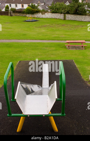 View Down a Childrens Slide with Empty Roundabout and Bench Seat in Playground Park at Kikcudbright Scotland United - Stock Photo