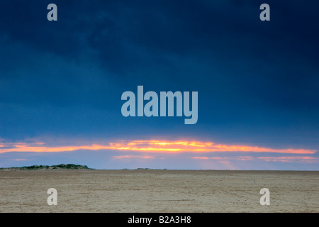 Sunset over the wide sandy beach at Wells next the Sea, Norfolk. - Stock Photo