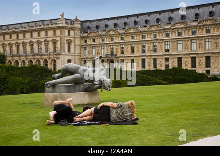 A female tourist lying on grass imitates pose of statue sculpture on green lawn of the Tuileries at Louvre while - Stock Photo
