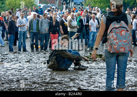 techno fan sitting in the mud during Love Parade 2008 in Dortmund Germany - Stock Photo