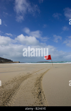 Red lifesaving flag flying on beach in sennen cove west Cornwall, England, UK - Stock Photo