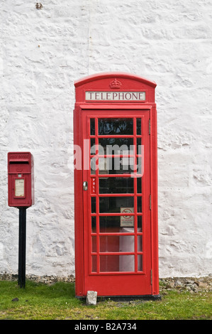 Red British telephone booth and rural post box next to white wall, Scotland - Stock Photo