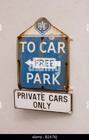 old blue and white rac car parking sign on white wall of building - Stock Photo