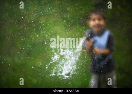 Hosepipe sprayed at a glass window Six year old boy Mixed race indian ethnic caucasian - Stock Photo