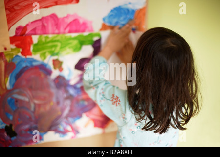 Five year old girl sticks artwork on her bedroom pinboard Mixed race indian ethnic - Stock Photo