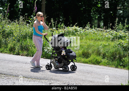 Mother pushing child in buggy out for a stroll along the many beautiful and interesting paths of the Upper Derwent - Stock Photo