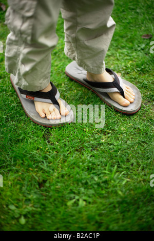 Six year old boy in father's flipflop sandals - Stock Photo