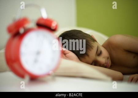 Boy aged six sleeps in his bed beside bright red alarm clock Mixed race indian english - Stock Photo