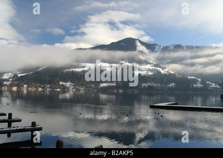 A magnificent view of an Alpine summit from the village of Zell Am See Austria with the morning fog lifting - Stock Photo
