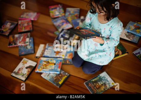 Five year old girl spends time choosing a DVD to watch in the afternoon - Stock Photo