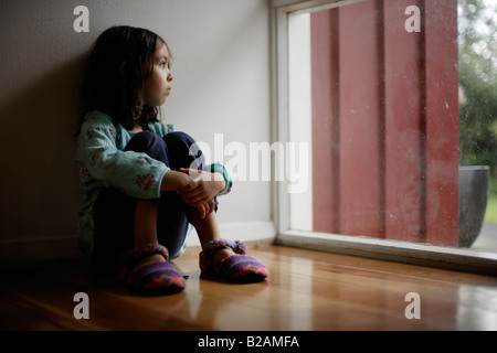 Portrait of little girl aged five sat on floor beside window Mixed race indian ethnic and caucasian - Stock Photo