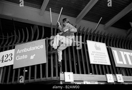 Football supporter climbing over a fence at Wembley Stadium to watch the 1996 FA Cup Final between Liverpool and - Stock Photo