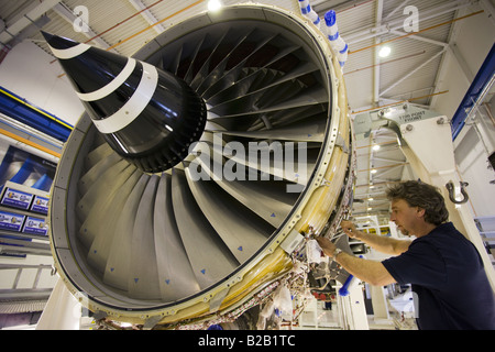 Engineer works on a Rolls Royce jet engine in the production factory Derbyshire United Kingdom - Stock Photo