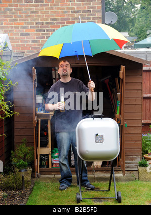 Man having a BBQ in his garden in the rain, UK - Stock Photo