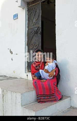 Young Muslim woman with child on steps by doorway Mutrah Muscat Oman - Stock Photo