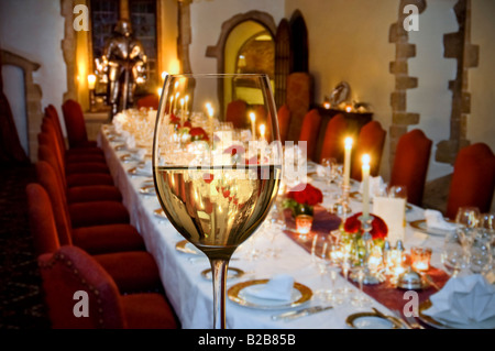 Glass of fine white wine in foreground with a formal seated candlelit dinner party table prepared in background - Stock Photo