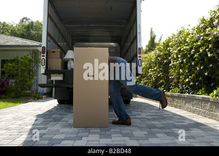 Young man climbing into large moving box - Stock Photo
