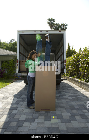 Young couple playing with large moving box - Stock Photo
