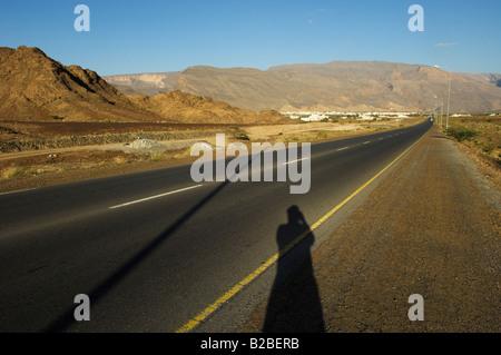Long straight desert road in Oman town of Al Mudaifi in backgroud near Nezwa - Stock Photo