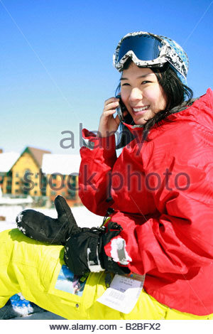 Asian skier talking on cell phone - Stock Photo