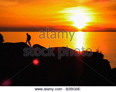Person on cliff at sunset - Stock Photo