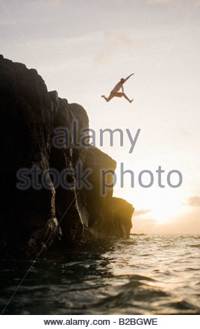 Man jumping from cliffs into ocean - Stock Photo